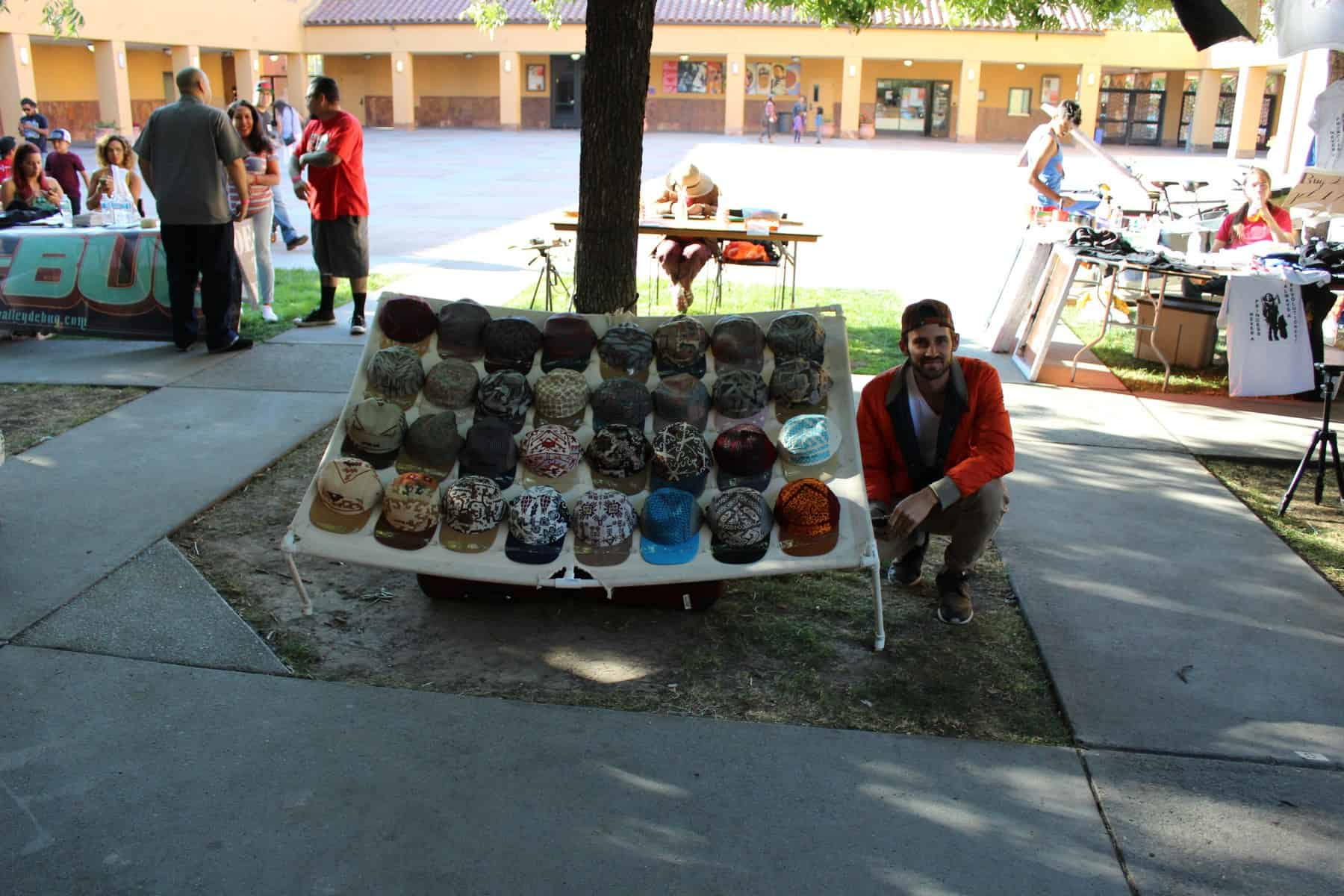 Young Man Selling Hats At Vendor Booth