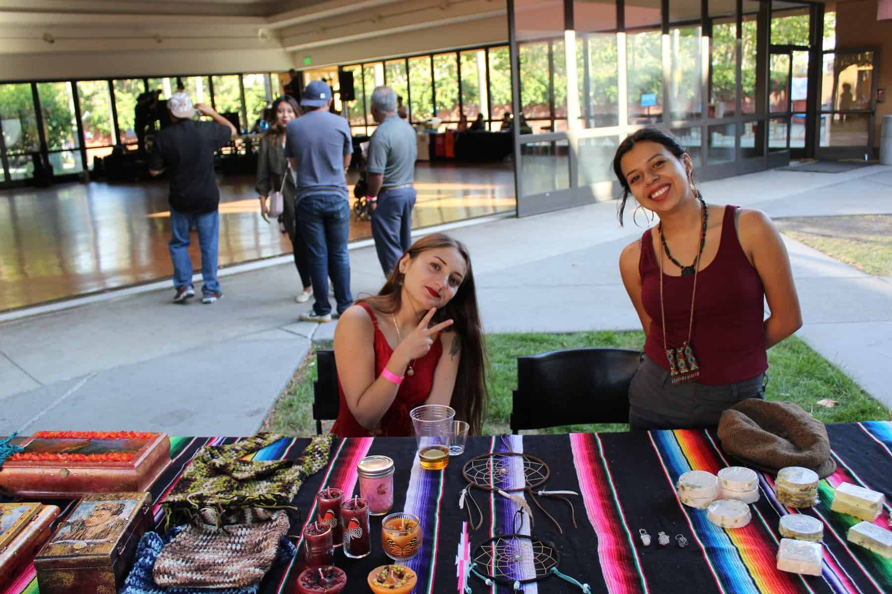 Two women posing at their vendor booth of dreamcatchers