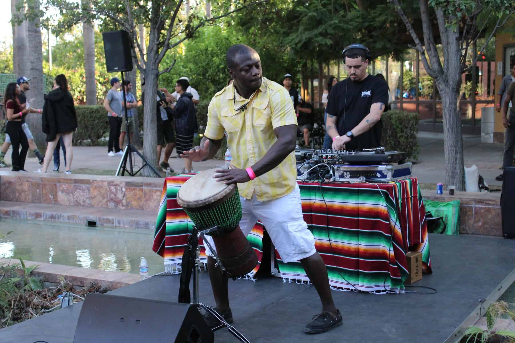 Man In Yellow Shirt Playing Drum With Hands