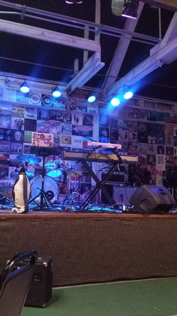 Stage with keyboard and drum kit, back wall is filled with posters