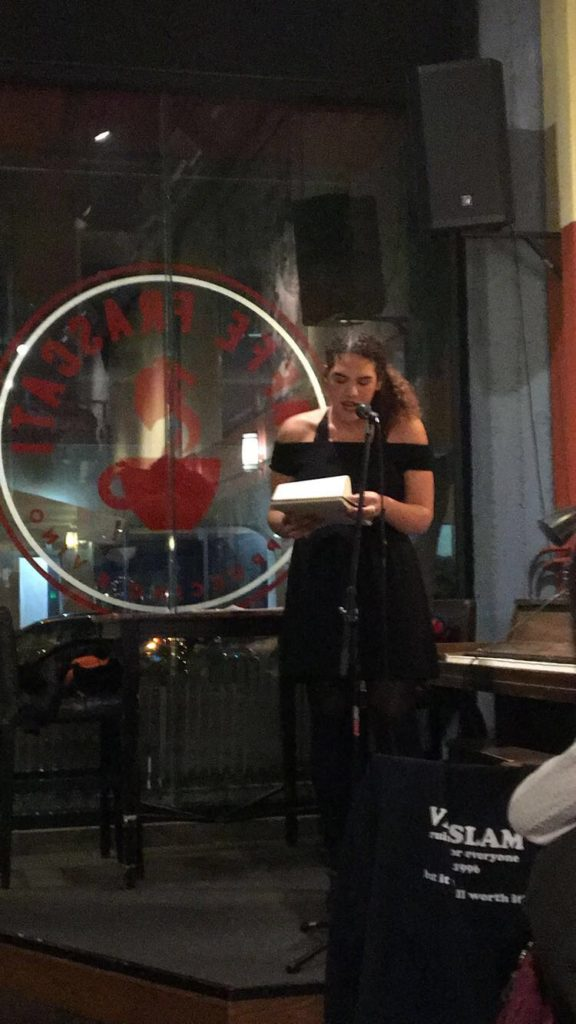 Woman Reading Paper At Coffee Shop Open Mic Event